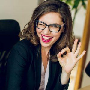 Uśmiechnięta kobieta w okularach pokazuje znak OK